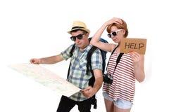 De jonge die kaart die van de de lezingsstad van het toeristenpaar losmakend richtlijn met rugzak van de meisjes de dragende reis stock afbeeldingen