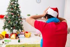De jonge die man thuis na Kerstmispartij wordt gedronken royalty-vrije stock fotografie