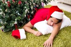 De jonge die man thuis na Kerstmispartij wordt gedronken stock foto