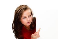 Jonge aantrekkelijke vrouw achter lege raad op witte achtergrond Stock Afbeeldingen