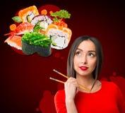 De jonge die sushi van de vrouwenholding met eetstokjes, op rood worden geïsoleerd stock foto's