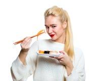 De jonge die sushi van de vrouwenholding met eetstokjes, op wit worden geïsoleerd stock afbeelding