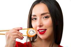 De jonge die sushi van de vrouwenholding met eetstokjes, op wit worden geïsoleerd royalty-vrije stock foto