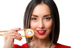 De jonge die sushi van de vrouwenholding met eetstokjes, op wit worden geïsoleerd stock afbeeldingen