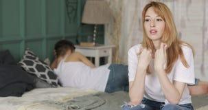 De jonge die vrouw door problemen in de verhoudingszitting ongerust wordt gemaakt in bed, haar vriend ligt dichtbij zich het afwe stock footage
