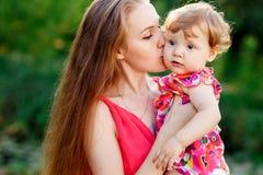 De jonge dochter van de moeder kussende baby in park Stock Foto