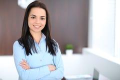 De jonge donkerbruine bedrijfsvrouw kijkt als een studentenmeisje die in bureau werken Spaanse of Latijns-Amerikaanse meisje stat Royalty-vrije Stock Fotografie