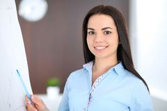 De jonge donkerbruine bedrijfsvrouw kijkt als een studentenmeisje die in bureau werken Spaanse of Latijns-Amerikaanse meisje stat Stock Afbeeldingen