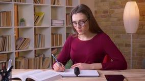 De jonge donkerbruine langharige vrouwelijke student die in oogglazen boek lezen maakt nota's zijnd aandachtig in bureau stock video