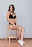 De jonge donkerbruine model stellende zitting van testschoten op ladder tegen muur voor de momentopnamenportefeuille van het mode Stock Fotografie