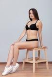 De jonge donkerbruine model stellende zitting van testschoten op ladder tegen muur voor de momentopnamenportefeuille van het mode Stock Foto's
