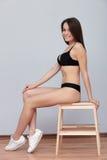 De jonge donkerbruine model stellende zitting van testschoten op ladder tegen muur voor de momentopnamenportefeuille van het mode Royalty-vrije Stock Afbeelding