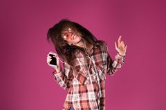 De jonge donkerbruine verslaafde van de meisjesmuziek luistert aan muziek op smartphone met oortelefoons stock afbeeldingen