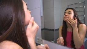 De jonge donkerbruine vrouw bereidt gezicht die voor make-up voor ochtendroom op huid toepassen stock video