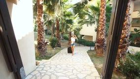 De jonge donkerbruine vrouw in borrels, zonnebril en hielen komt met koffer tussen palmen in hotel Vakantie stock video