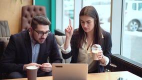 De jonge donkerbruine vrouw die een milkshake houden en geeft instructies aan een partner die op laptop richten stock video