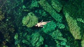 De jonge donkerbruine vrouw drijft en speelt in een natuurlijke pool van een cenote in Mexico stock footage