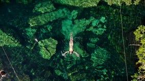 De jonge donkerbruine vrouw drijft en speelt in een natuurlijke pool van een cenote in Mexico stock videobeelden