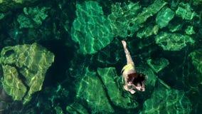 De jonge donkerbruine vrouw drijft en speelt in een natuurlijke pool van een cenote in Mexico stock video