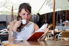 De jonge donkerbruine vrouw drinkt koffie in een koffie Royalty-vrije Stock Afbeelding
