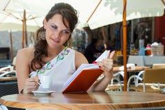 De jonge donkerbruine vrouw drinkt koffie in een koffie Royalty-vrije Stock Afbeeldingen