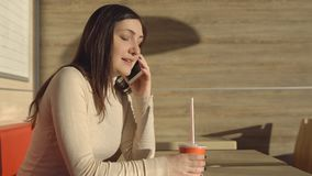 De jonge donkerbruine vrouw in een koffie drinkt sap en het spreken op de telefoon Stock Fotografie