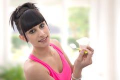 De jonge donkerbruine vrouw eet een yoghurt Stock Afbeelding