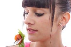 De jonge donkerbruine vrouw eet salade, omhoog sluit Stock Afbeelding