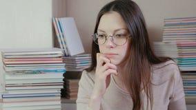 De jonge donkerbruine vrouw in glazen denkt stock video