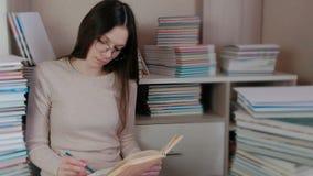 De jonge donkerbruine vrouw in glazen schrijft de nota's zittend op de vloer onder de boeken stock video