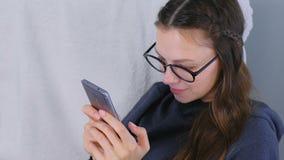 De jonge donkerbruine vrouw in glazen typt een bericht thuis op een mobiele telefoonzitting in leunstoel stock videobeelden