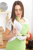 De jonge donkerbruine vrouw in groene schort kookt of eet verse salade in de keuken Huisvrouw die houten lepel houden en Royalty-vrije Stock Foto's