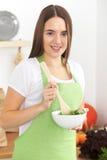 De jonge donkerbruine vrouw in groene schort kookt of eet verse salade in de keuken Huisvrouw die houten lepel houden en Royalty-vrije Stock Afbeeldingen