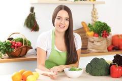 De jonge donkerbruine vrouw kookt of eet verse salade in de keuken Huisvrouw die houten lepel in rechts haar houden Stock Foto's