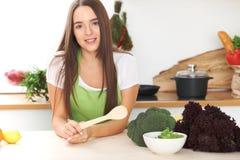 De jonge donkerbruine vrouw kookt of eet verse salade in de keuken Huisvrouw die houten lepel in rechts haar houden Stock Foto