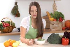 De jonge donkerbruine vrouw kookt of eet verse salade in de keuken Huisvrouw die houten lepel in rechts haar houden Stock Fotografie