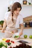 De jonge donkerbruine vrouw kookt en proeft verse salade in de keuken Huisvrouw die houten lepel in haar hand houden Royalty-vrije Stock Foto's