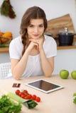 De jonge donkerbruine vrouw kookt en proeft verse salade in de keuken Huisvrouw die houten lepel in haar hand houden Stock Afbeelding