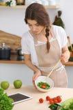 De jonge donkerbruine vrouw kookt en proeft verse salade in de keuken Huisvrouw die houten lepel in haar hand houden Royalty-vrije Stock Afbeeldingen