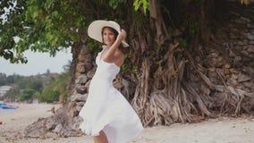 De jonge donkerbruine vrouw met lang haar in witte drees en hoed kijkt het achter wenken voor zich op tropisch strand langzaam stock footage