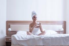 De jonge donkerbruine vrouw ontspant met koffie in bed Stock Fotografie