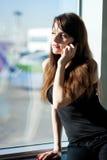De jonge donkerbruine vrouw spreekt op mobiele telefoon Stock Fotografie