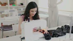 De jonge donkerbruine vrouw zit achter naaimachine en stikt fabriekstextiel Zij concentreerde zich en inspireerde in proces en stock footage