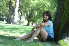 De jonge donkerbruine vrouw zit onder een boom Stock Afbeelding