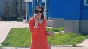 De jonge donkerbruine vrouw in zonnebril spreekt het schreeuwen en het zweren op de telefoon naast de blauwe bouw stock video