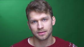 De jonge donkerbruine zakenman draait hoofd om te ontkennen en niet akkoord te gaan zijnd aandachtig op groene achtergrond stock video