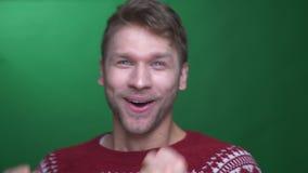 De jonge donkerbruine zakenman in sweater toont extreem geluk en het gesticuleren vreugdevol op groene achtergrond stock footage