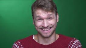 De jonge donkerbruine zakenman toont positieve vermaak en vreugde in camera op groene achtergrond stock videobeelden