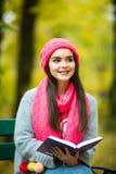 De jonge donkerbruine zitting op de gevallen herfst gaat in een park, lezing een weg boek Stock Fotografie