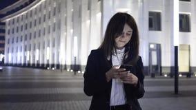 De jonge donkere haired vrouw met een smartphone en hoofdtelefoons loopt in een nachtstad stock video